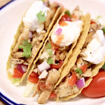 3 Grilled chicken tacos with sour cream and salsa on corn shells