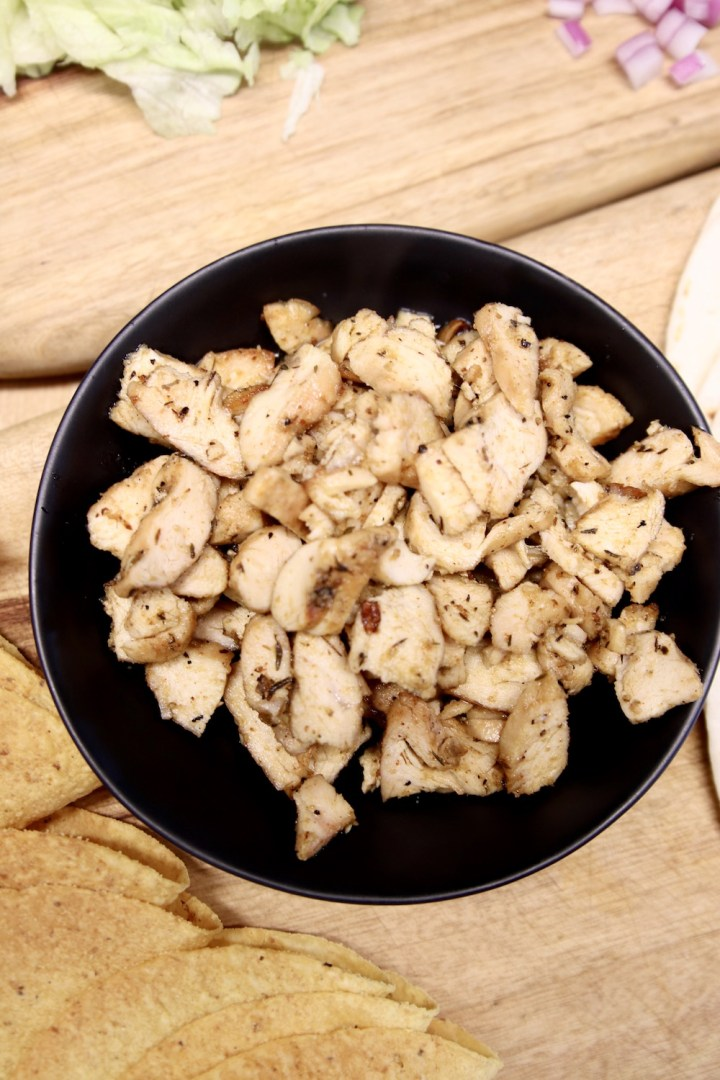 black bowl of chopped grilled chicken