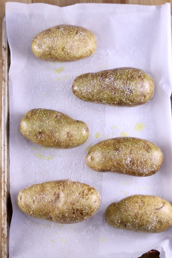 Russet potatoes on a lined baking sheet rubbed with olive oil and salt