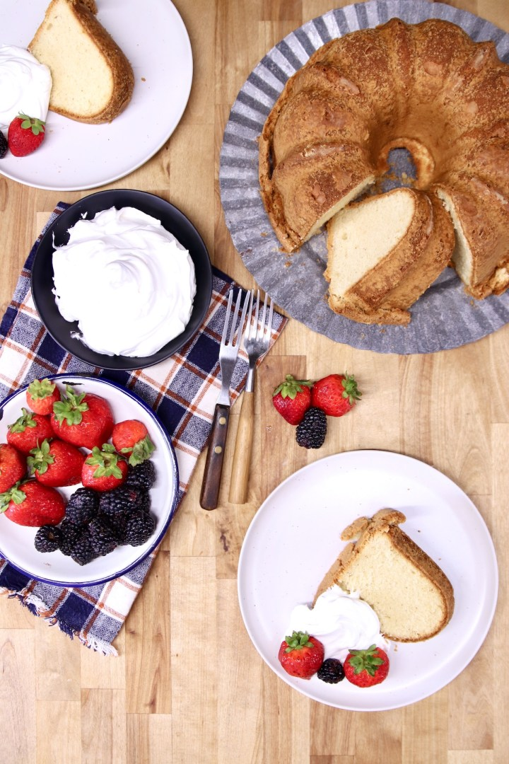 overhead photo of cake on cake plate, 2 slices on saucers with whipped cream & berries, bowls of whipped cream and berries