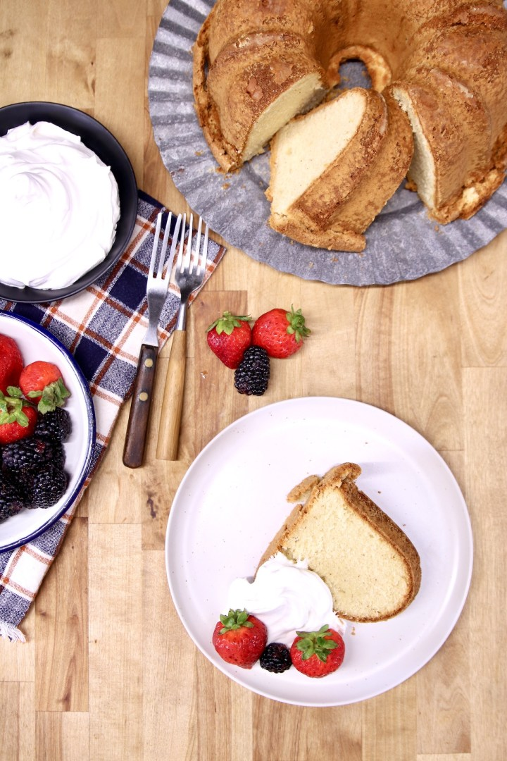 slice of pound cake with berries and whipped cream, cake on platter, bowls of whipped cream, berries