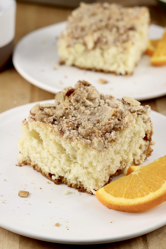 Slices of streusel coffee cake with orange slices - 2 plates