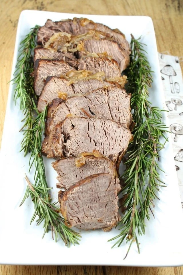 Sliced Pot Roast on a white platter, garnished with fresh rosemary