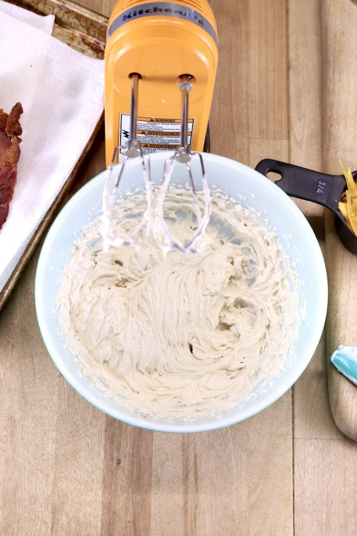 Cream cheese mixture whipped in a bowl until creamy, orange hand mixer with the bowl