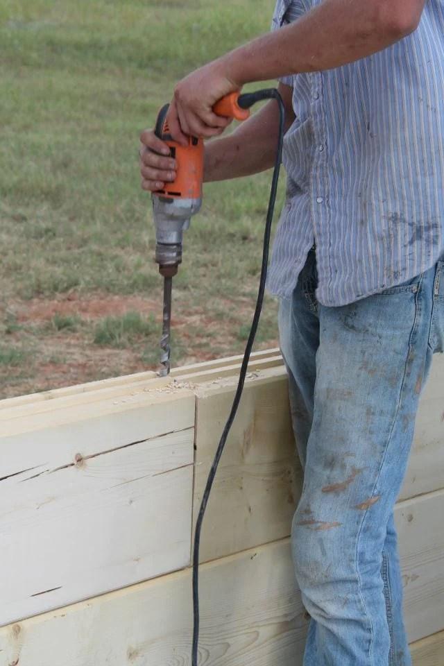 Auger Bit drilling holes for dowel rods to strengthen log joints for log cabin  missinthekitchen #LogCabinSaturday
