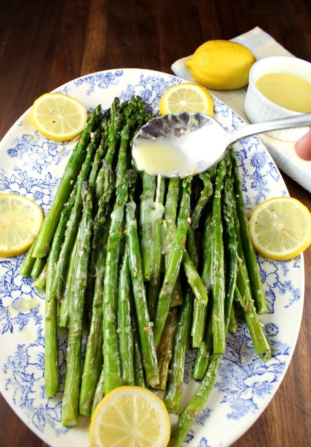 Drizzling Lemon Sauce over Garlic Roasted Asparagus from MissintheKitchen.com