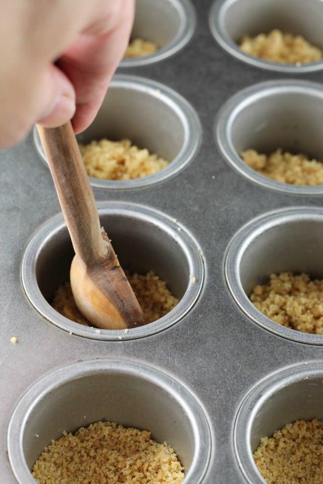 Adding crust for Mini Turtle Cheesecakes ~ MissintheKitchen.com