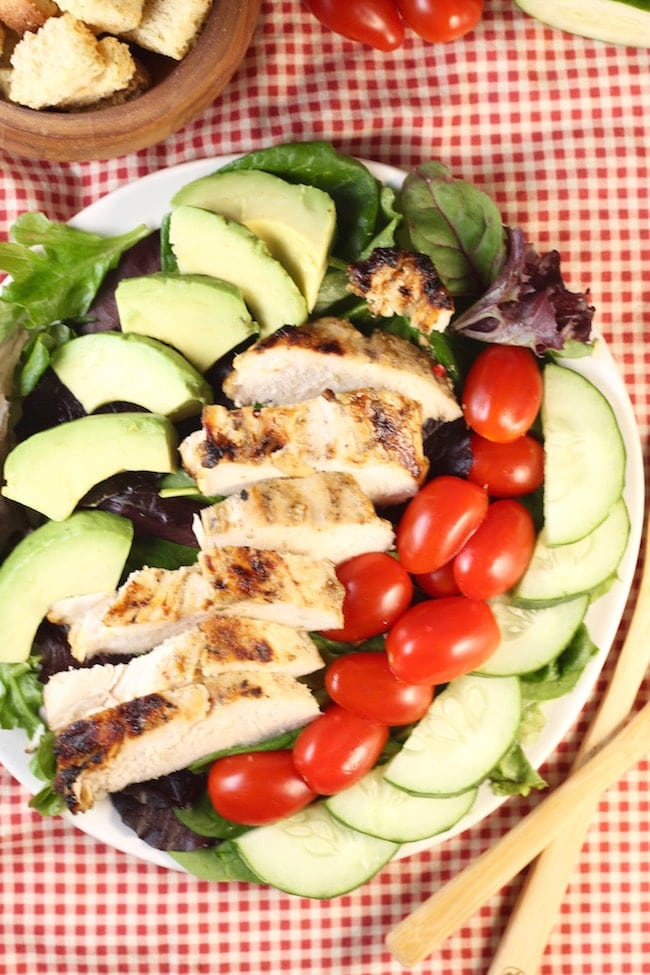 Grilled-Chicken-Salad-on-a-plate-with-tomatoes-avocado-cucumber- placed-on-napkin