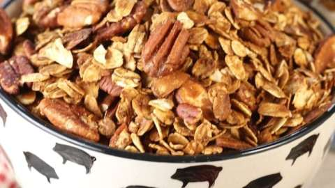 Easy granola recipe with pecans and almonds in a black and white bowl with blueberries and strawberries on the white back ground
