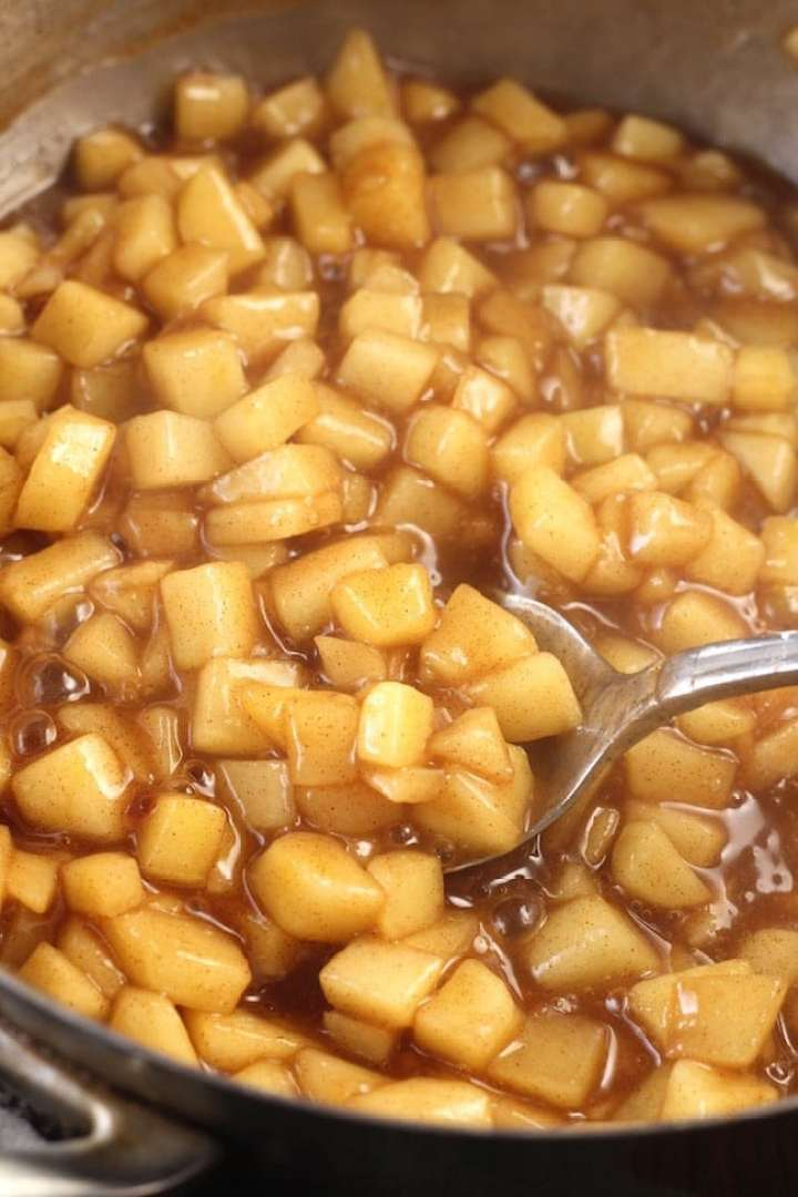 Cooked diced apples with cinnamon sugar and nutmeg with a spoon