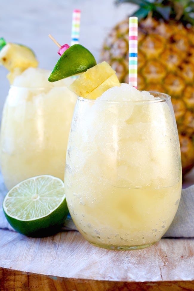 Pineapple Limeade Slush in stemless wine glasses garnished with fresh limes, pineapple. Whole Pineapple in background