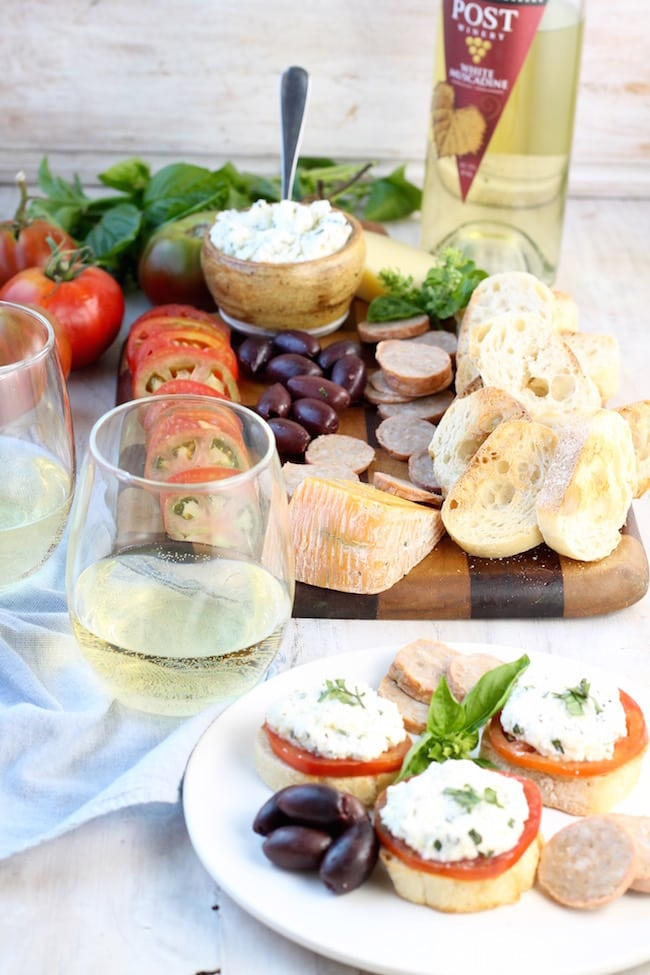 Fresh Heirloom Tomato and Herbed Ricotta Bruschetta and charcuterie board with sausage, cheese and muscadine wine