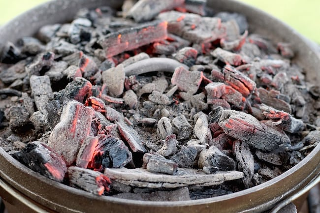 Topping the Dutch Oven with Coals for Short Ribs and potatoes campfire meal