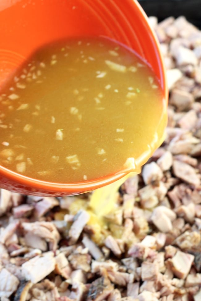 Pouring orange and lime juice mixture over pork for carnitas