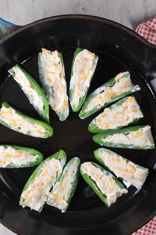 Stuffing jalapeño poppers with cream cheese, garlic and shredded cheddar cheese
