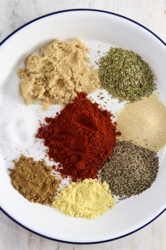 Paprika, garlic, oregano, pepper and spices for Blackened Seasoning on a white plate