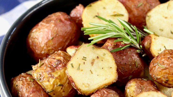 Air Fryer Roasted Potatoes with fresh rosemary in a black bowl, blue check towel
