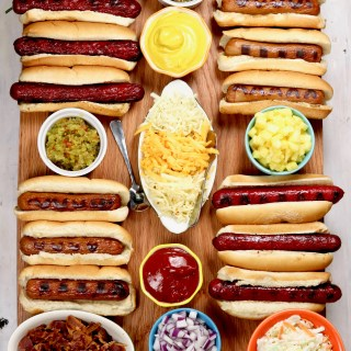 Board with grilled hot dogs and toppings