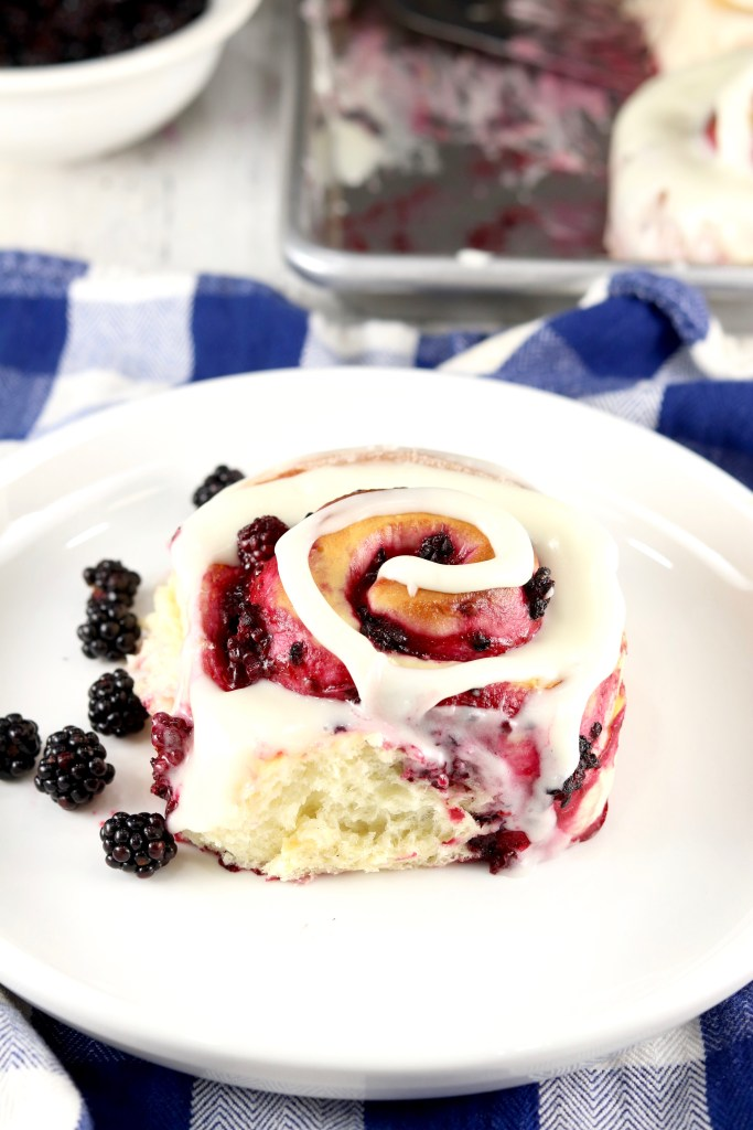 White plate with sweet roll filled with blackberry filling and topped with cream cheese icing in a swirl.