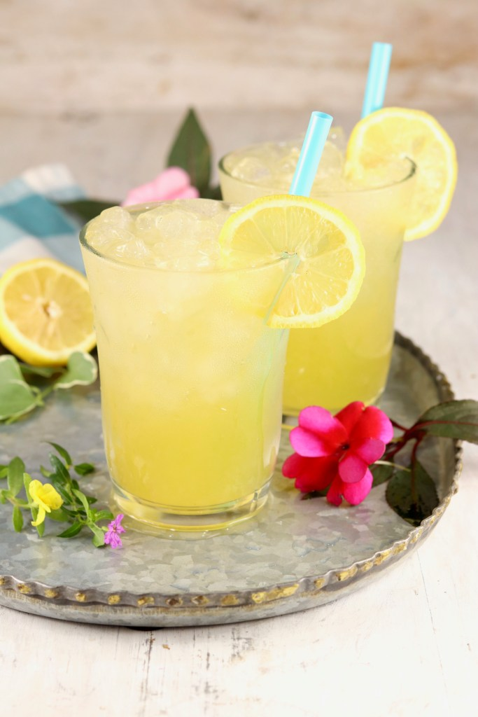 Galvanized platter with 2 glasses of lemonade, fresh flowers and lemons garnish the tray