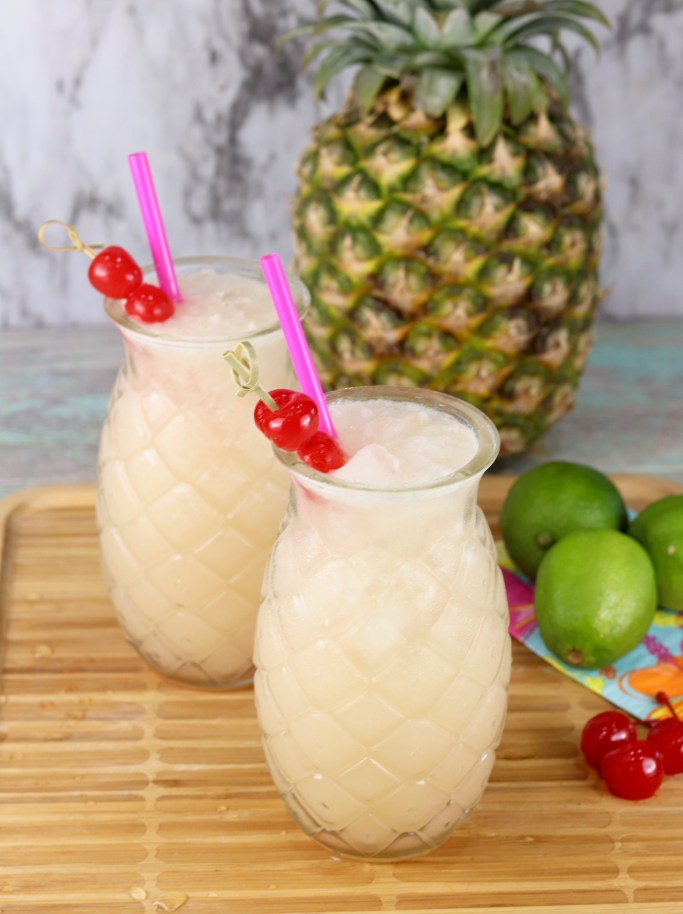 Wine cocktail served in pineapple glasses garnished with cherries and pink straws