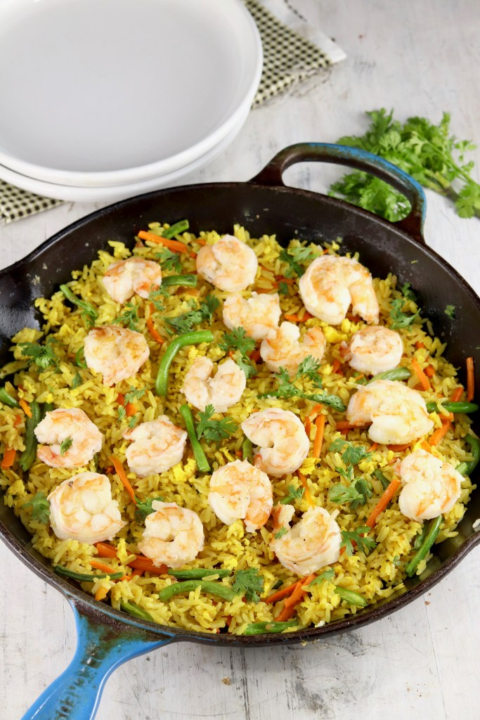 White plates and skillet of fried rice with shrimp, carrots, green beans and cilantro