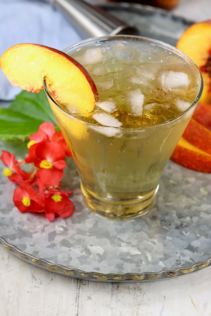 Peach Old Fashioned Cocktail garnished with a fresh peach slice