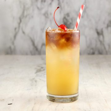 Pineapple Rum cocktail with a straw made with black spiced rum