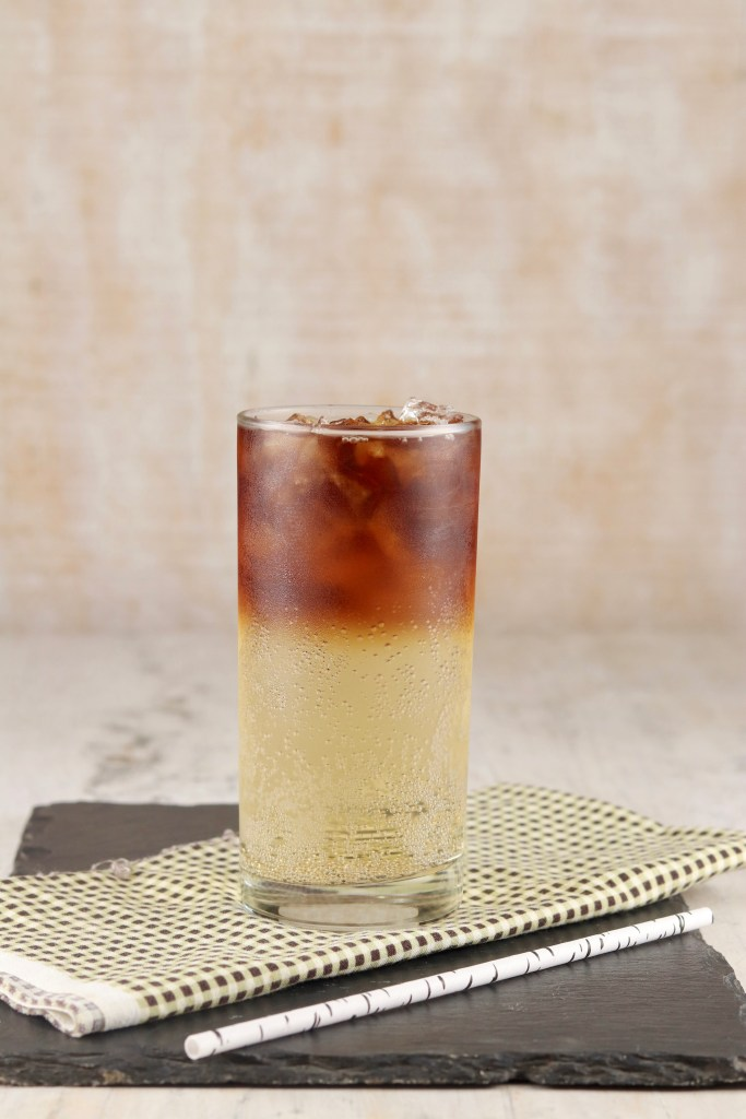 Glass of ginger ale with black rum floating on top