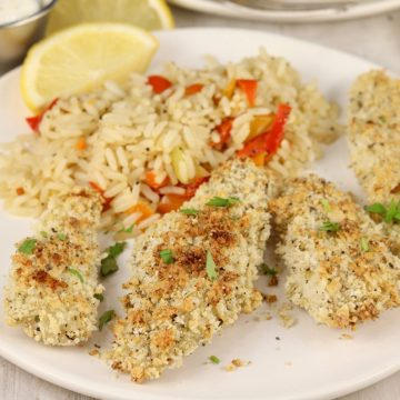 Baked fish sticks on a white plate with rice and fresh lemon slice