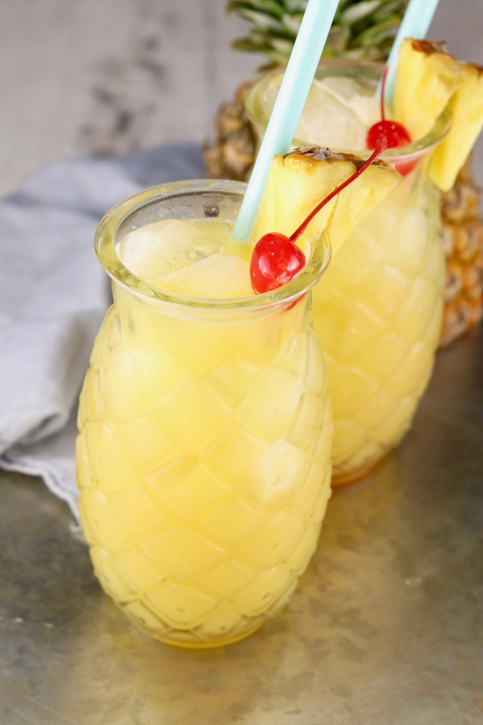 Pineapple drink glasses with cocktails garnished with cherries