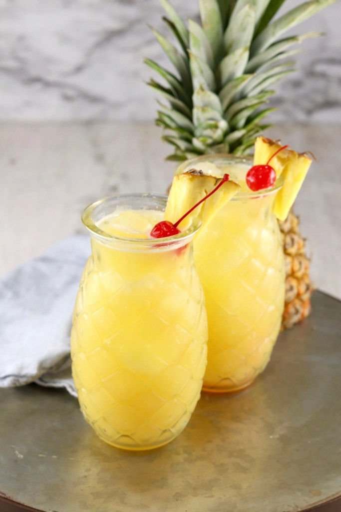 Pineapple Fuzzy Navel drink in a pineapple shaped glass