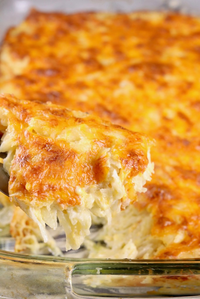 Cheesy Hashbrown Casseole in a clear baking dish, scooped with a spatula