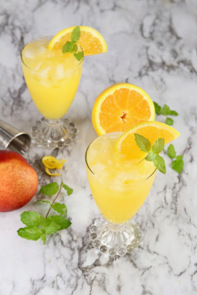 Orange juice cocktail with mint garnish
