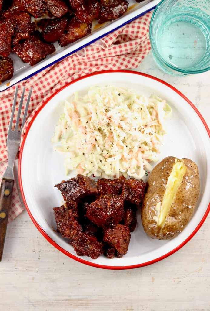 Burnt Ends Barbecue on a plate with baked potato and coleslaw
