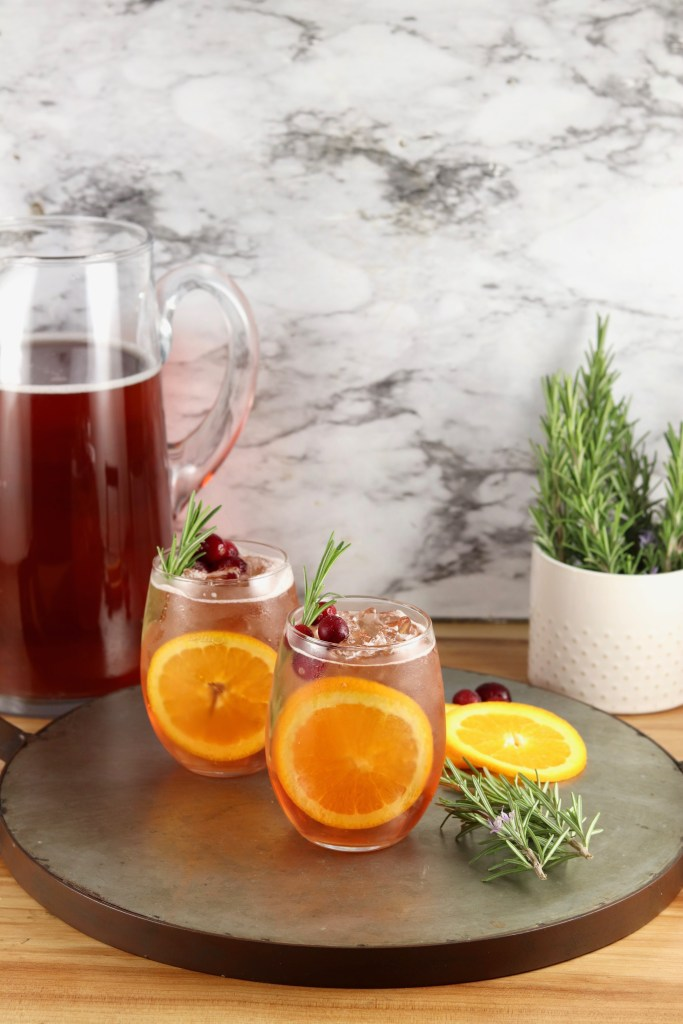 Wine Punch in a pitcher, 2 stemless wine glasses with punch, fresh rosemary garnish
