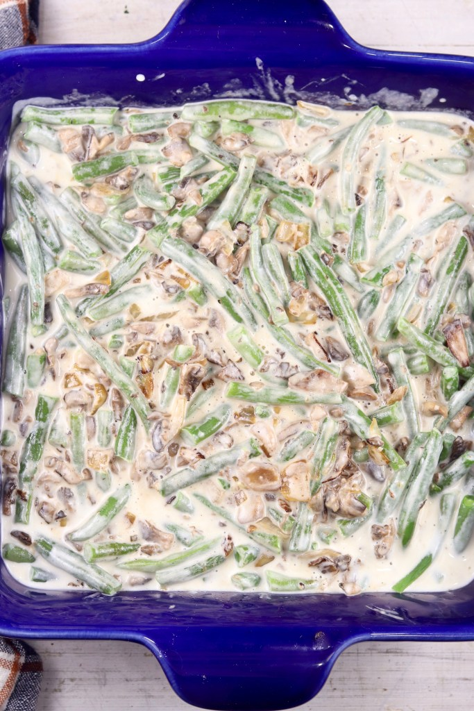 Creamy green bean casserole in a blue baking dish