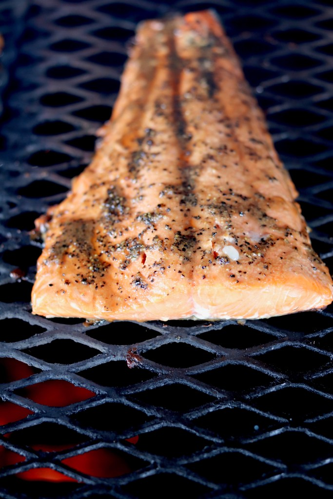 Grilling salmon over wood fired grill
