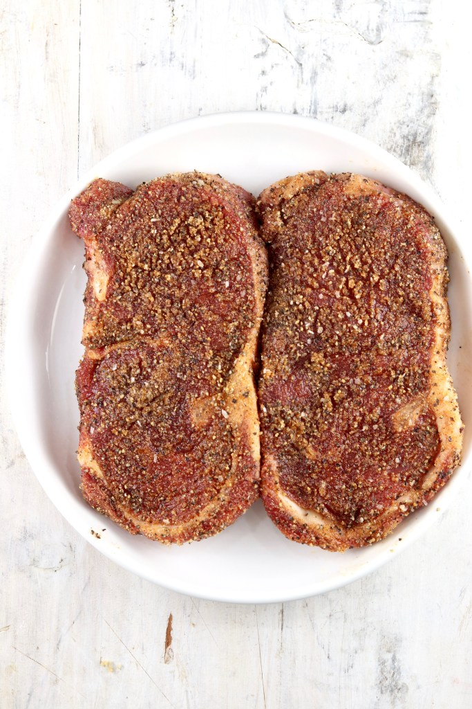 Seasoned ribeye steaks on a plate