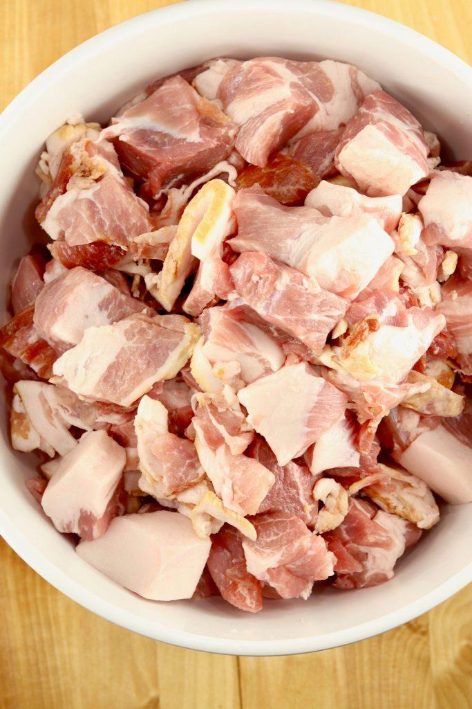 Schweineschulter in Stücke geschnitten und mit Speckstücken in einer Schüssel vermischt