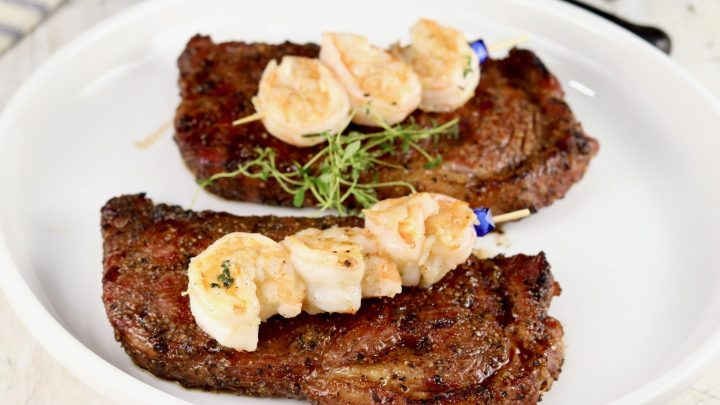 steak and shrimp on a white plateSurf and Turf is the ultimate dinner for entertaining guests or date night. Grilled ribeye steaks topped with garlic butter shrimp is a hearty and delicious meal that is sure to impress.