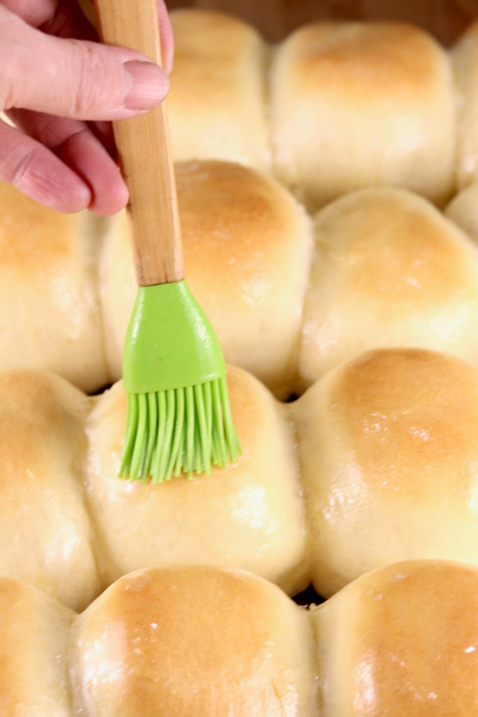 brushing dinner rolls with butter