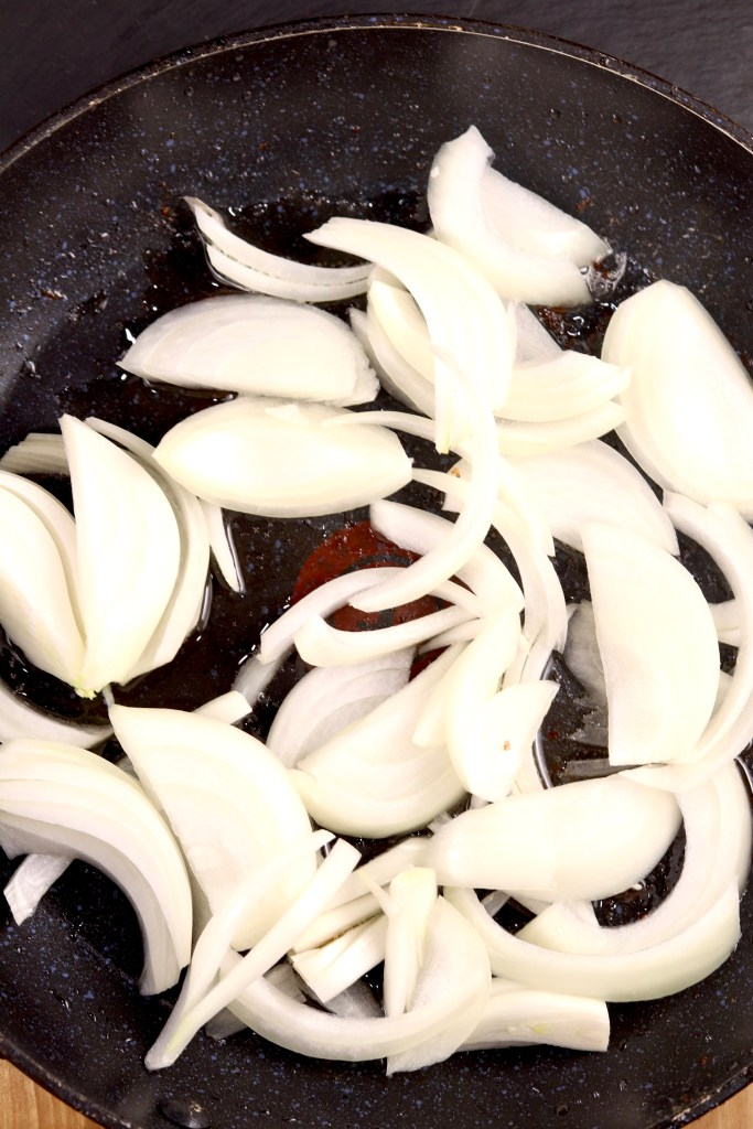 sliced onions in a skillet for fried cabbage