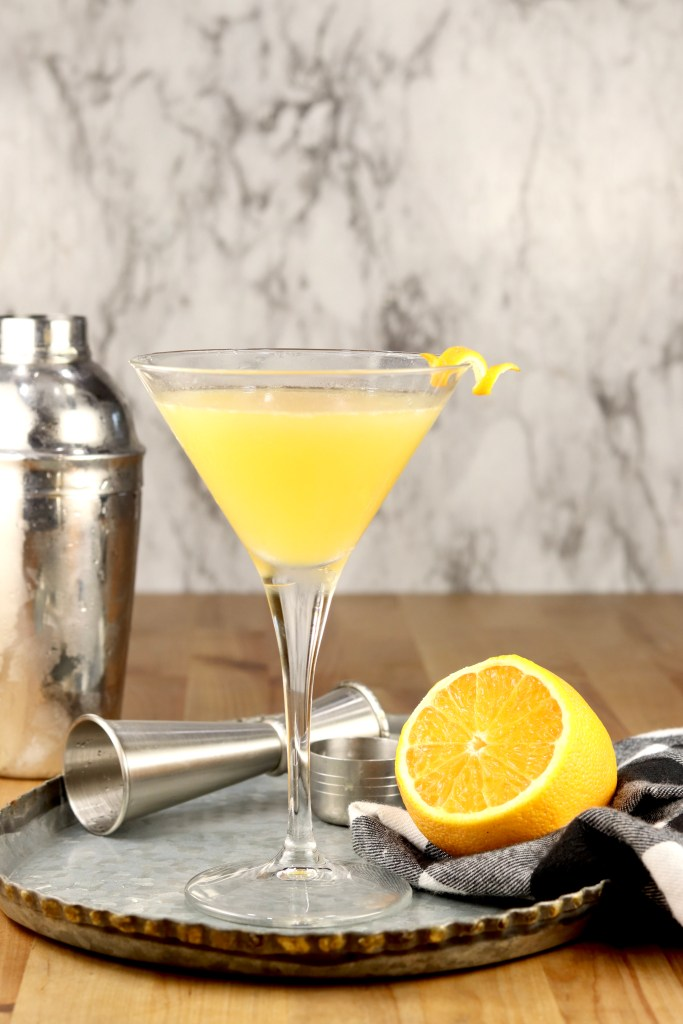 Bees Knees Cocktail with a shaker, jigger and sliced orange on a tray