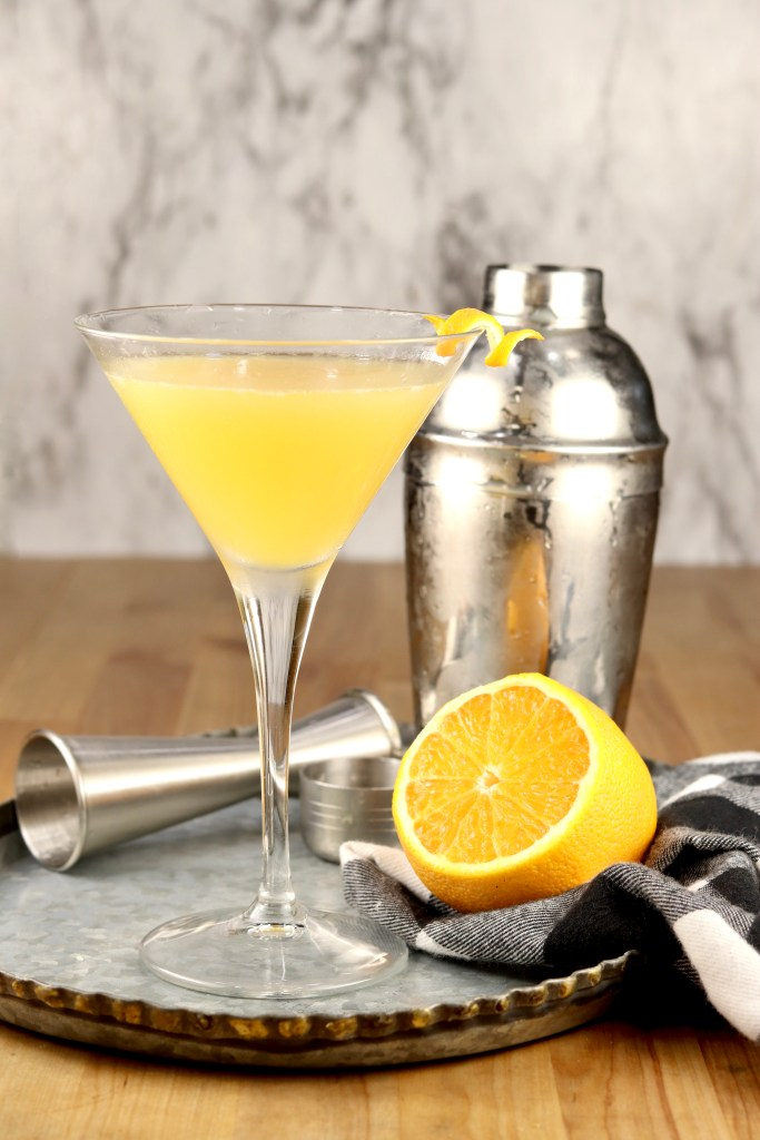 Bees Knees Gin Cocktail with half lemon on a tray + Cocktail shaker