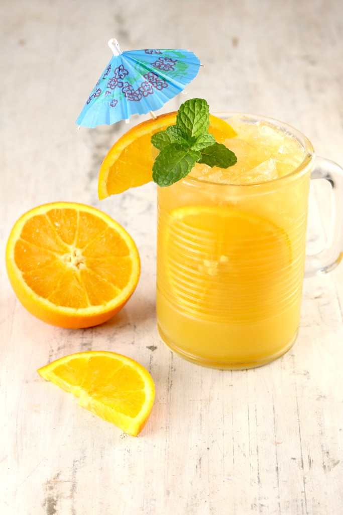 Mug of Orange Cocktail with vodka and rum, garnish of orange slice, mint and an umbrella