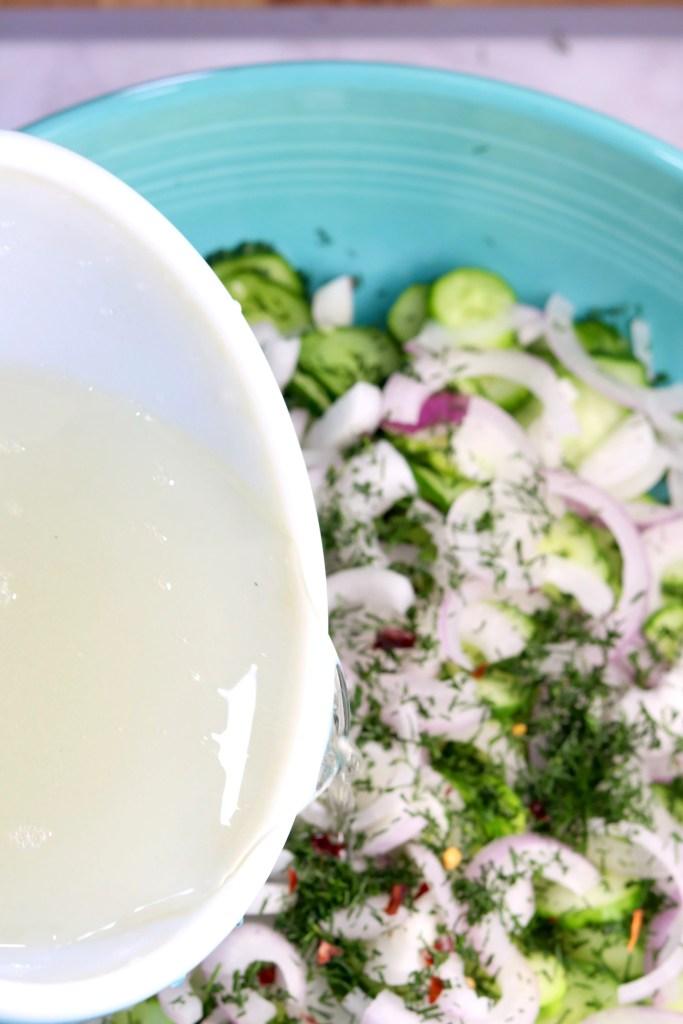 Pouring vinegar dressing over cucumber salad