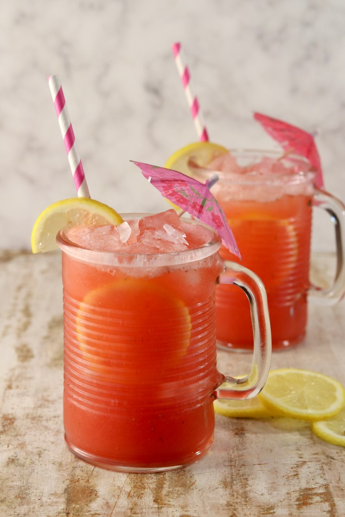 2 mugs of strawberry lemonade, lemon and drink umbrella garnishes