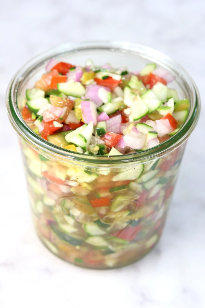Chopped cucumber tomato and onion salad in a weck jar