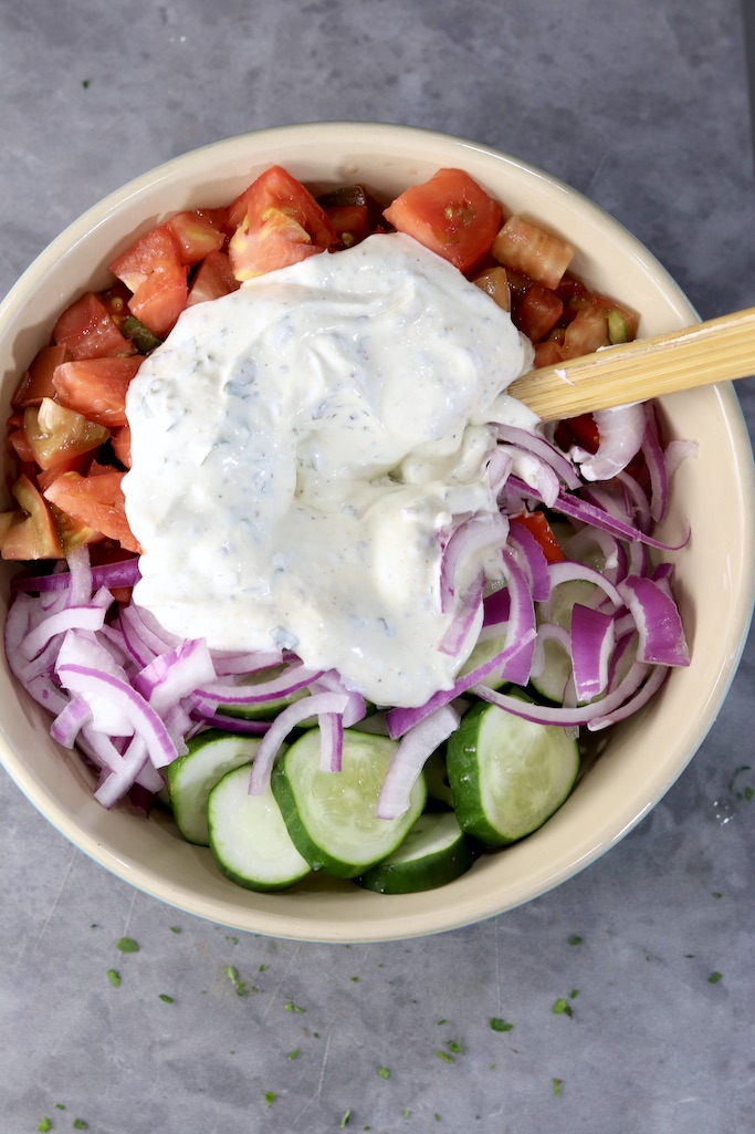 Creamy dressing over chopped tomatoes, cucumbers and onions in a bowl